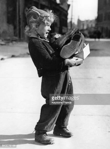 Enfant les bras chargés de chaussures dans une rue de la ville occupée par l'armée américaine à Hanovre Allemagne le 19 avril 1945
