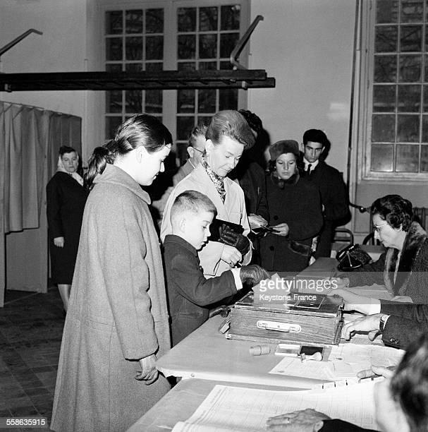Enfant mettant un bulletin de vote dans une urne à l'occasion de l'élection présidentielle en France le 5 décembre 1965
