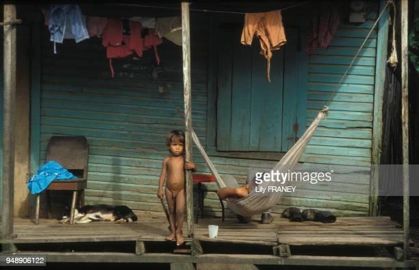 Enfant nu sur la terrasse d'une maison à Puerto Cabezas en septembre 1984 Nicaragua