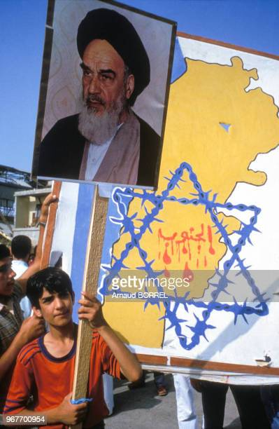 Enfant portant un panneau à l'effigie de l'ayatollah Rouhollah Khomeini lors d'une manifestation du Hezbollah contre Israël le 21 juin 1985 à...