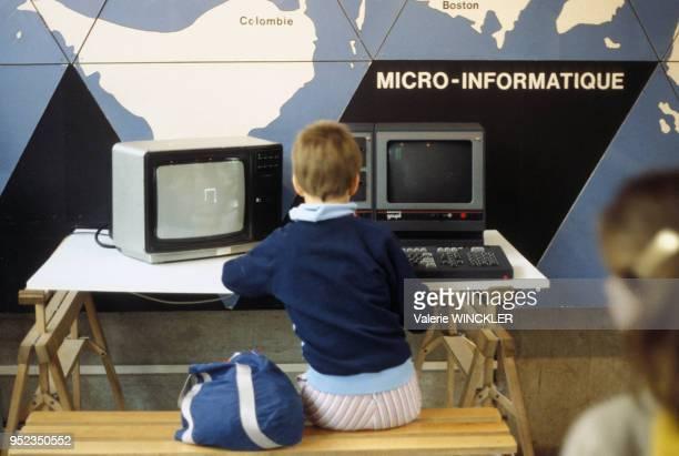 Enfant utilisant un ordinateur lors d'une exposition au Centre mondial informatique à Paris circa 1980 France