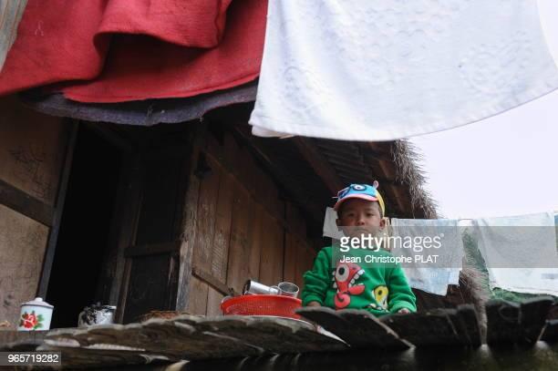 Enfant Wa du village de Weng Ding dans sa maison, le 17 decembre 2013, Yunnan, Chine.