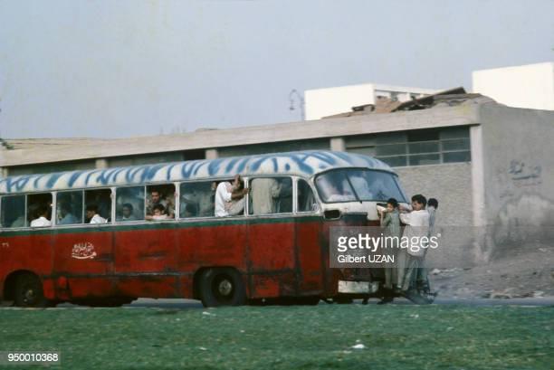 Enfants accrochés à l'arrière de l'autobus au Caire Egypte