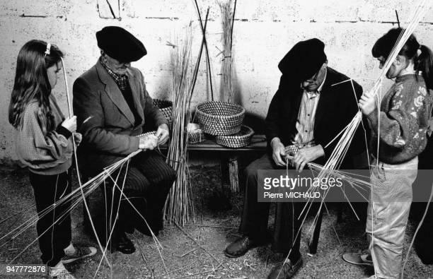 Enfants avec des vanniers lors de la visite de l'atelier d'une association d'artisants retraités en Bretagne France