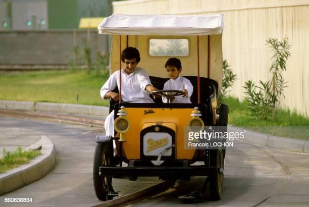 Enfants à bord d'un vieux modèle automobile dans le parc d'attractions de l'an 2000 à Koweït City en mai 1984 Koweït