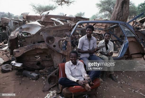 Enfants chargés de la récupération des pièces dans une casse de voitures à Niamey en décembre 1986 Niger
