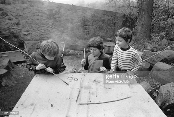 Enfants dessinant avec des bouts de bois brûlés à Orsay dans l'Essonne en 1980 France
