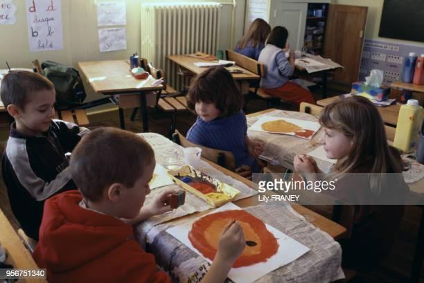 Enfants faisant de la peinture en classe dans une école primaire à Gentilly en 1995 dans le ValdeMarne France