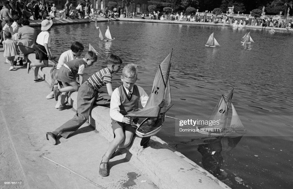 Enfants jouant avec des modèles réduits de bateaux au bord du bassin ...