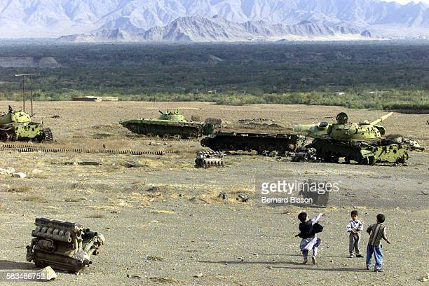 Enfants jouant dans un cimetiere de chars datant de l'occupation sovietique