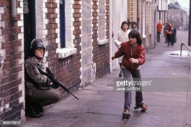 Enfants jouant près des forces de l'ordre britannique qui ont été déployées dans Belfast après les émeutes provoquées par la mort de Bobby Sands en...