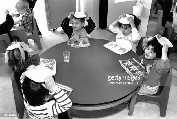Enfants mettant leur assiette sur la tête avant de manger dans la crèche du Mail à Paris France