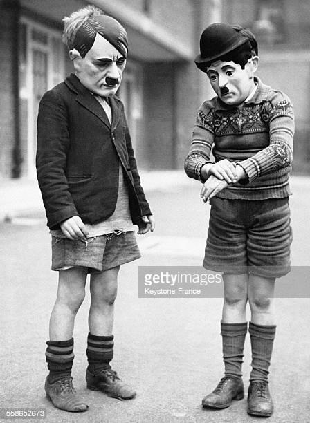 Enfants portant des masques représentant Adolf Hitler et Charlie Chaplin afin d'en comparer la moustache à Londres RoyaumeUni