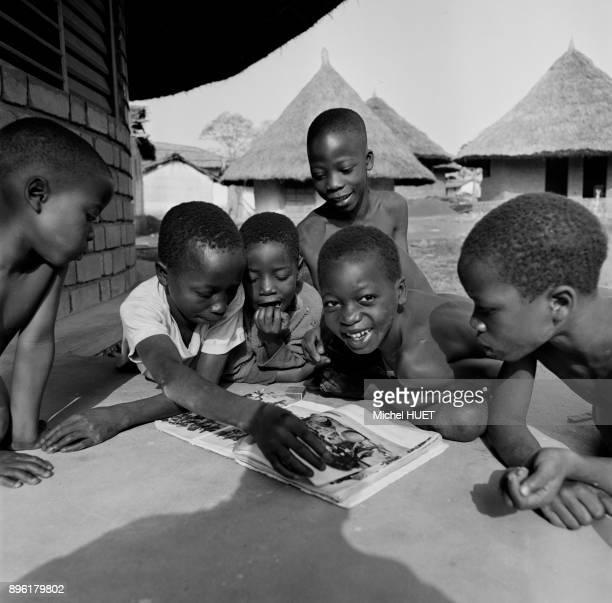 Enfants regardant un livre d'images en Cote d'Ivoire