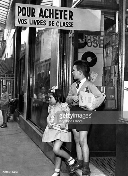Enfants sortant d'une librairie avec leurs livres scolaires sous le bras à Paris France le 20 septembre 1958