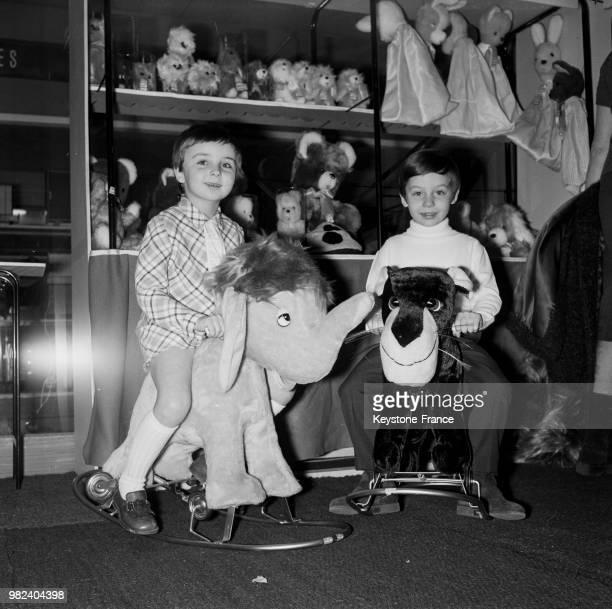 Enfants sur des animaux à bascule au 8ème salon international du jouet à la porte de Versailles à Paris en France le 2 février 1969
