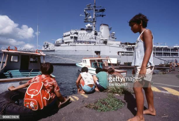 Enfants sur le port devant le navire de la marine française Jeanne d'Arc en janvier 1985 à Papeete à Tahiti en Polynésie française