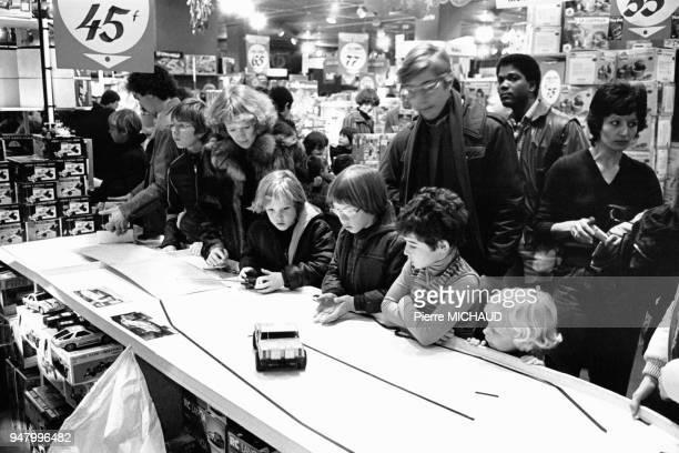 Enfants testant une voiture télécommandée dans le rayon jouets d'un grand magasin avant Noël en France en 1983