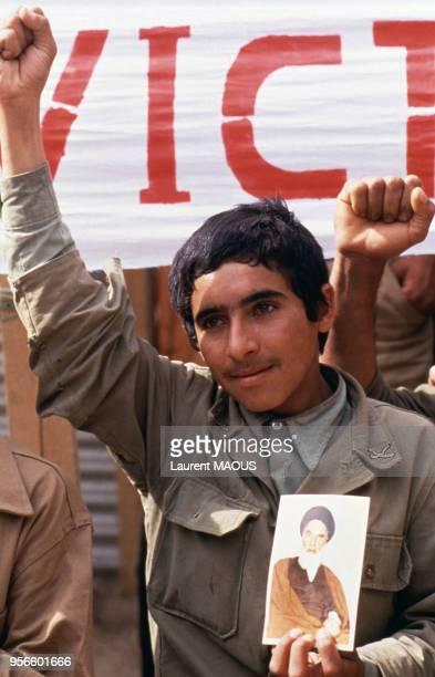 Enfant-soldat iranien tenant un portrait de Khomeiny lors de l'offensive 'Victoire indéniable' en mars 1982 en Iran.