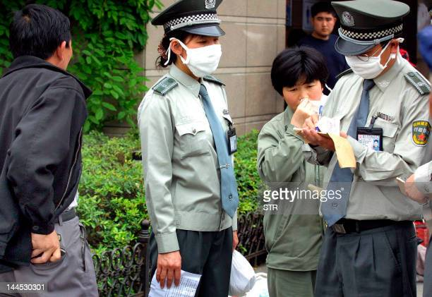 Enforcement officers wearing masks write up a fine of 50 yuan after catching a man for spitting on a street in the eastern Chinese city of Hangzhou...