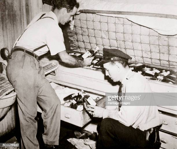 Enforcing prohibition Norfolk Virginia USA 1920s Law enforcement agents examining at a cache of 191 pint bottles found underneath a sailor's mattress...