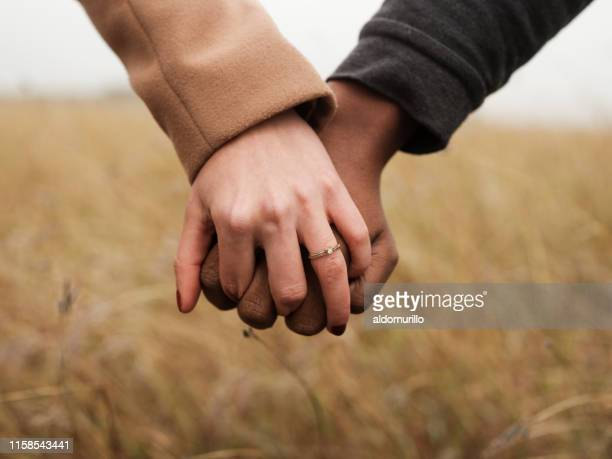 engaged couple holding hands - engagement stock pictures, royalty-free photos & images