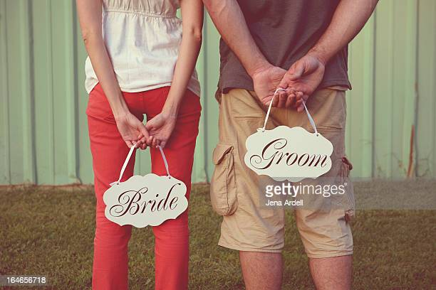 Engagement Couple Holding Bride and Groom Signs