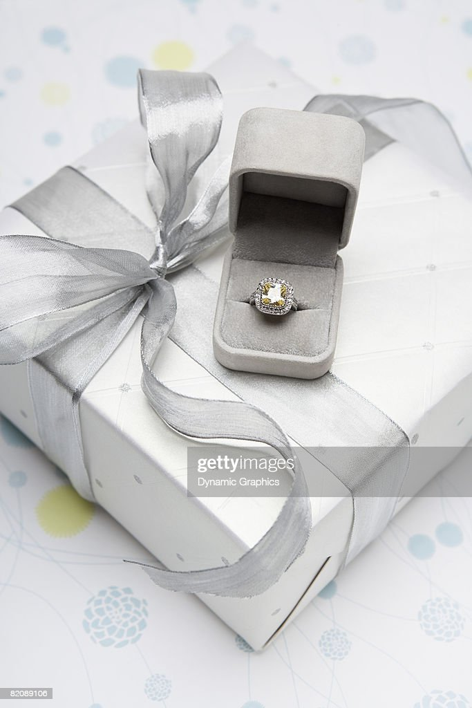 Engagement ring and wedding present : Stock Photo