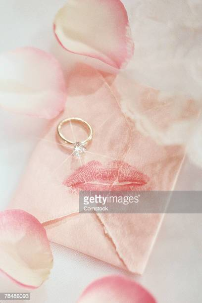 Engagement ring on letter with rose petals