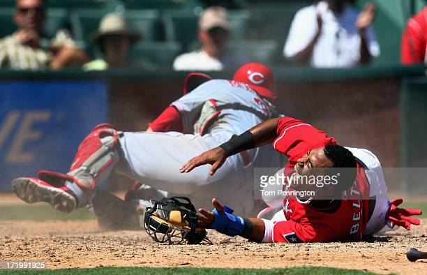 Engel Beltre of the Texas Rangers reacts in pain after a collision at home plate to score against catcher Devin Mesoraco of the Cincinnati Reds in...