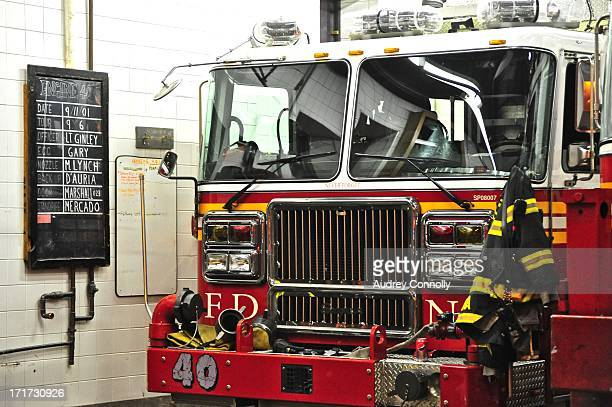 CONTENT] Engine Company FDNY Fire engine inside house with blackboard with names of lost fire fighters from 9/11 and uniforms New York City Ladder Co...