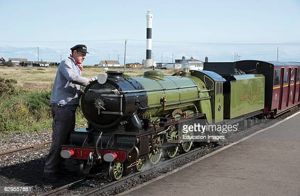 Engine driver polishing the Green Goddess loco which operates a passenger service between Hythe and Dungeness in Kent UK