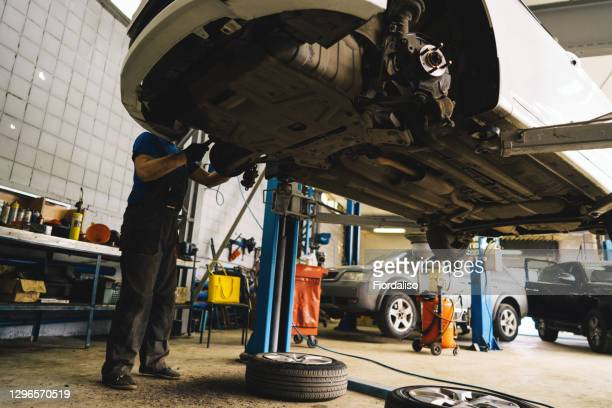 engine oil drain unit. car on a lift in a car service. - dirty stock pictures, royalty-free photos & images