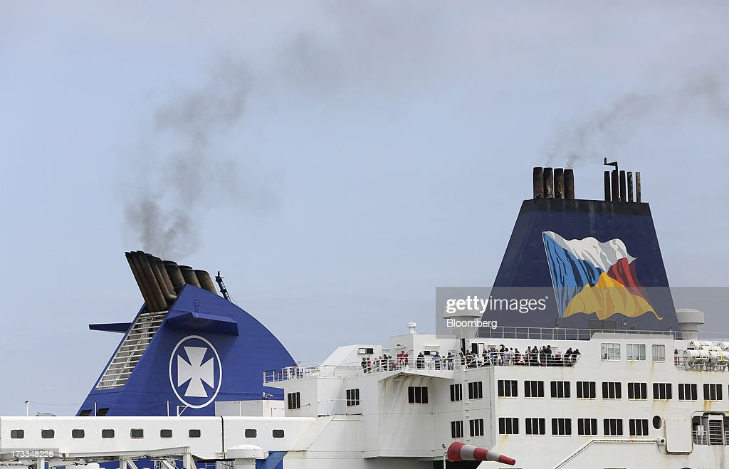 Engine smoke rises from the funnels of DFDS A/S, left, and P&O passenger ferries as they sit docked at the Port of Calais in Calais, France, on Thursday, July 11, 2013. Groupe Eurotunnel SA was barred by the U.K. Competition Commission from operating a ferry service between France and Dover in the U.K. on concern it would give it too much dominance on the Channel traffic route. Photographer: Chris Ratcliffe/Bloomberg via Getty Images