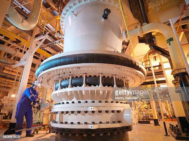 Engineer adjusting seawater valve in power