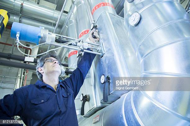 engineer adjusting valve in power station - sigrid gombert stock pictures, royalty-free photos & images