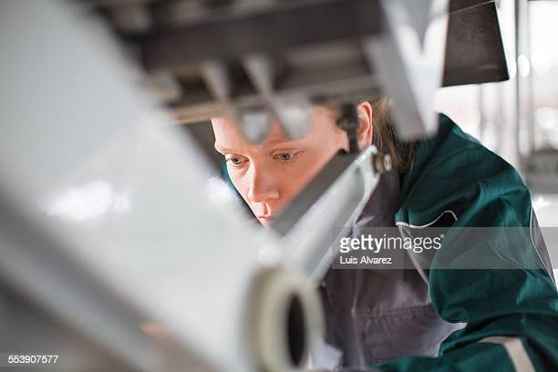Engineer analyzing airplane part in hangar