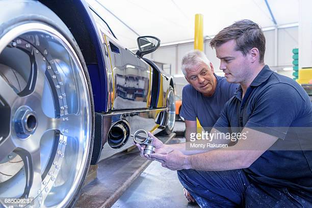 Engineer and apprentice discussing exhaust valve on sports car in research and development facility of factory