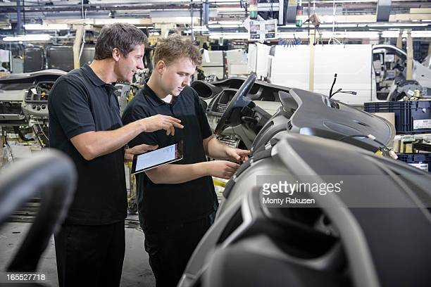 Engineer and apprentice discussing work with digital tablet on production line in car factory
