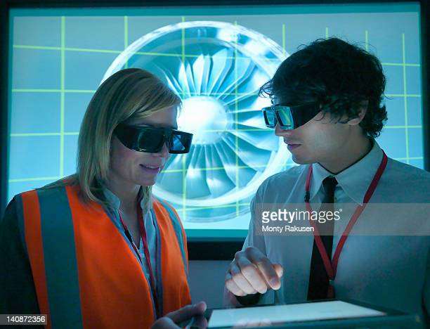 Engineer and apprentice in 3D glasses discussing engine on 3D screen