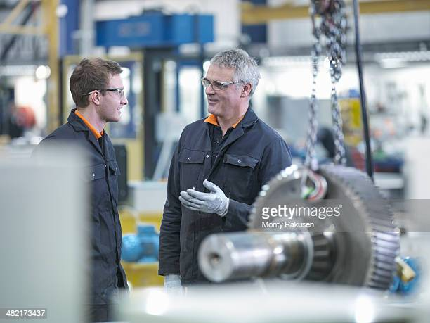 Engineer and apprentice in discussion next to gear wheel at work station in factory