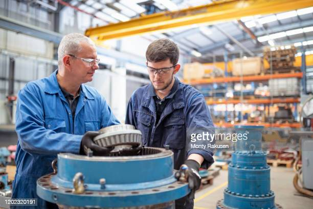 engineer and apprentice installing bearings into pump house in electrical engineering factory - expertise stock pictures, royalty-free photos & images