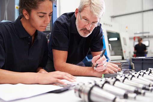 Engineer And Apprentice Planning CNC Machinery Project 484376424