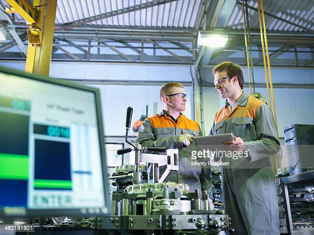 Engineer and apprentice using digital tablet at work station in factory