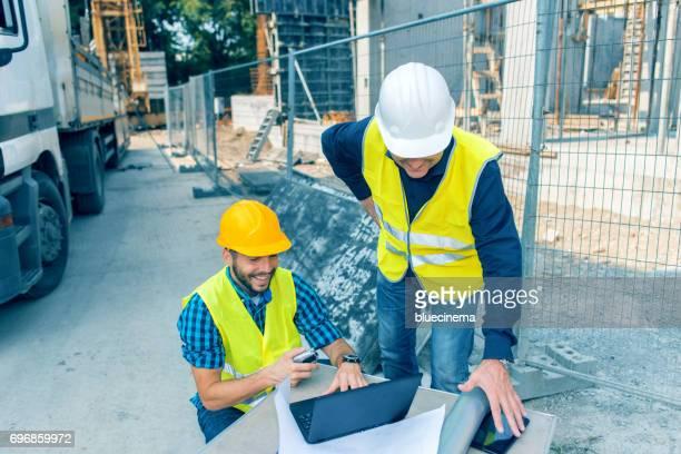 Ingenieur en architect kijken blauwdrukken op bouwplaats