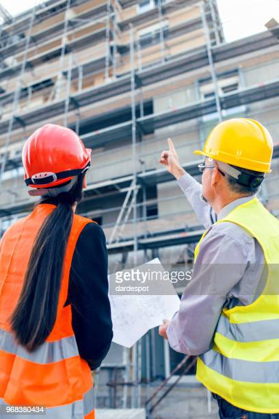 Engineer and architect looking at blueprints on construction site