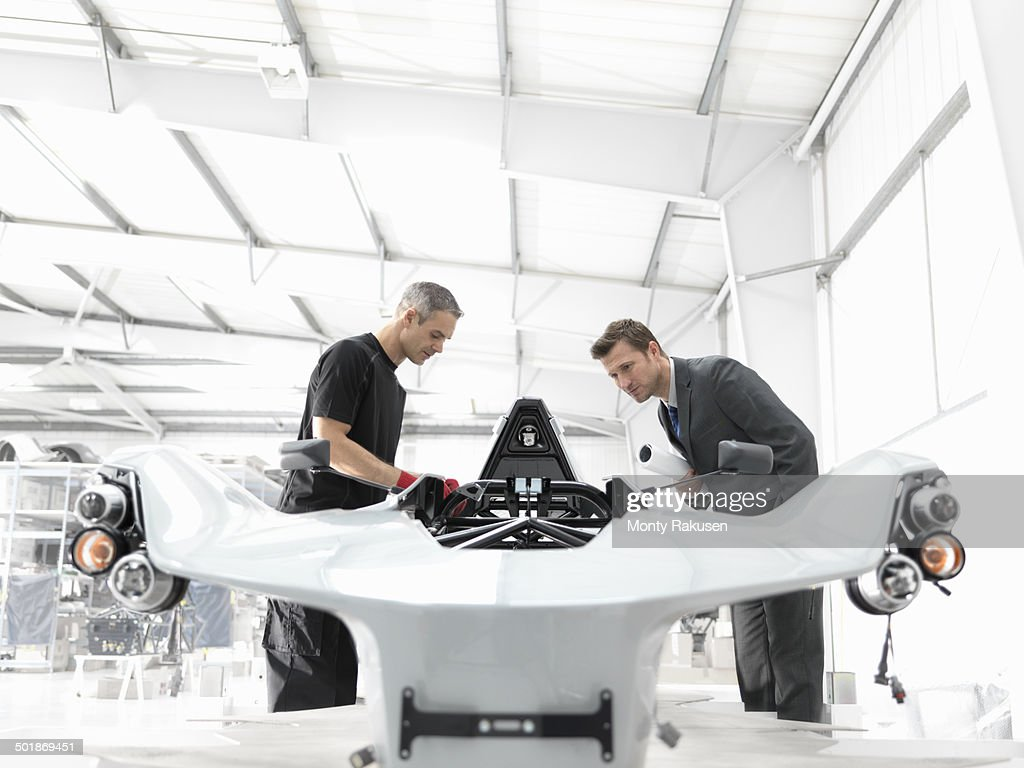 Engineer and automotive designer inspecting part-built supercar in car factory : Stock Photo