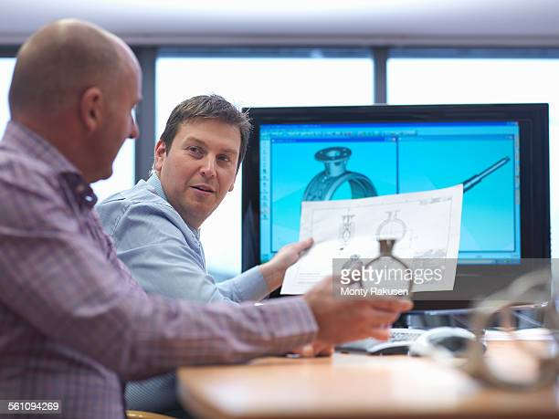 Engineer and client inspecting automotive part at desk