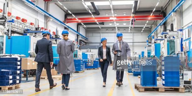 ingenieur en bedrijfsleider wandelen door een fabriek - bouwvakkershelm stockfoto's en -beelden