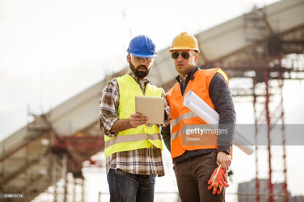 Engineer and construction manager looking at blueprint on site stock engineer and construction manager looking at blueprint on site stock photo malvernweather Image collections